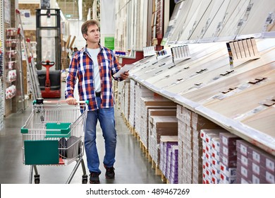 Man chooses floorboard for home renovation in store