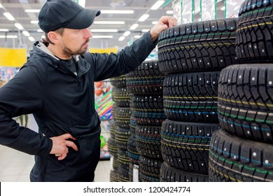 a man chooses new tires in the store.