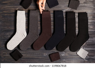 A man chooses socks! Set of winter classic colored  socks, flatlay on a wooden background