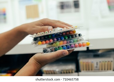 Man choosing buying stationery in store preparing for first day in school. Closeup on buyer hands holding goods. Busy blurred shopping indoors background