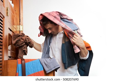Man choosing casual clothes form wardrobe. One men throwing clothes from closet isolated on white