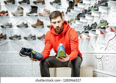 Man choosing trail shoes for hiking sitting in the fitting room of the modern sports shop