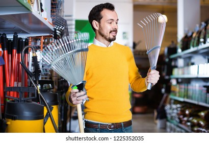 Man choosing various tools in garden equipment shop