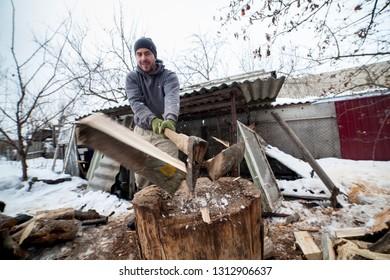 Man chopping cleaving doing wood work outside woodcutter/lumberjack