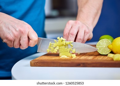 Man chopping fresh ginger on a wooden board for a recipe