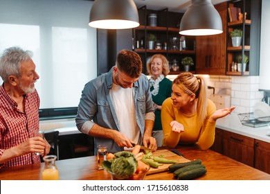 Man is chopping vegetables for a meal with his sister, mother and father standing next to him. They are having fun together.