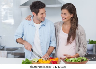 Man chopping vegetables next to his pregnant partner in the kitchen