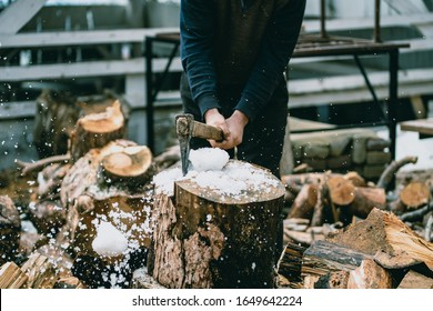 Man is chopping wood with vintage axe. Detail of flying pieces of wood on log with sawdust.