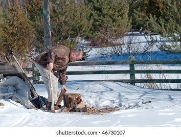 Man chopping wood in the winter.