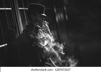 A man with a cigarette in a hat and a raincoat on the street of a night city.