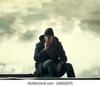 A man with a cigarette in his jacket on a background of a stormy sky