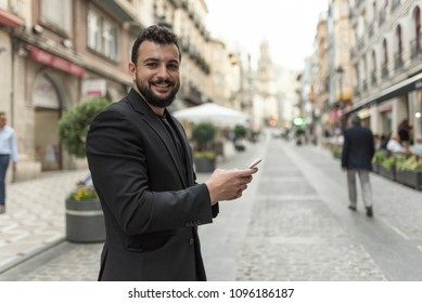 Man in the city with smartphone looking at camera