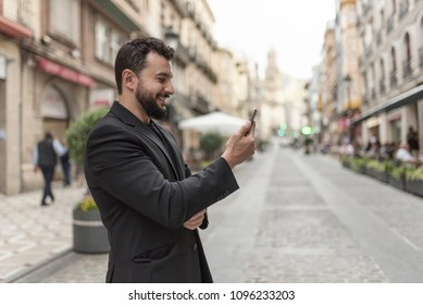 Man in the city with smartphone looking messages