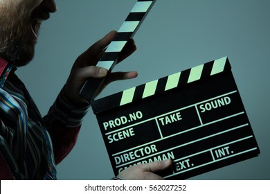 Man with clapperboard cinema. Bearded man movie production assistant