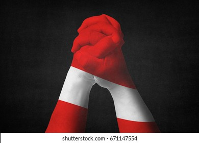 Man clasped hands patterned with the AUSTRIA flag.Black background