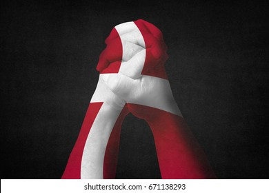Man clasped hands patterned with the DENMARK flag,Black background.