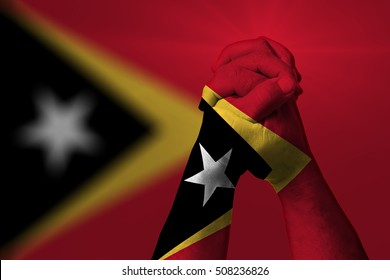 Man clasped hands patterned with the EAST TIMOR flag