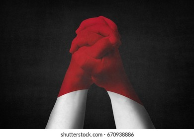 Man clasped hands patterned with the INDONESIA flag,Black background.