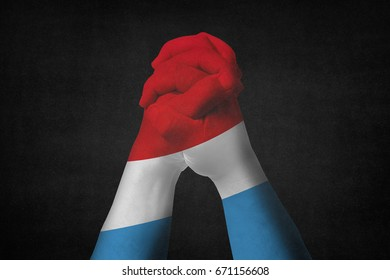 Man clasped hands patterned with the LUXEMBOURG flag.Black background
