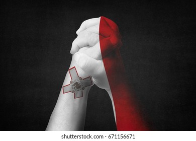 Man clasped hands patterned with the MALTA flag.Black background