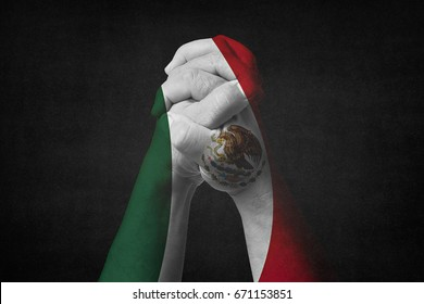 Man clasped hands patterned with the MEXICO flag.Black background