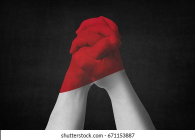Man clasped hands patterned with the MONACO flag.Black background
