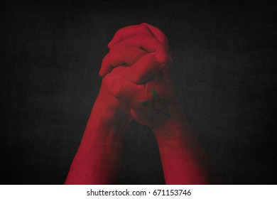 Man clasped hands patterned with the MOROCCO flag.Black background