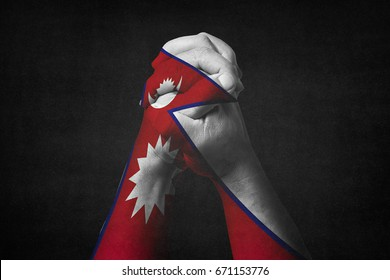 Man clasped hands patterned with the NEPAL flag.Black background