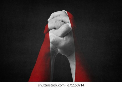 Man clasped hands patterned with the PERU flag.Black background