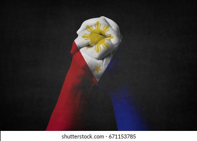 Man clasped hands patterned with the PHILIPPINES flag.Black background