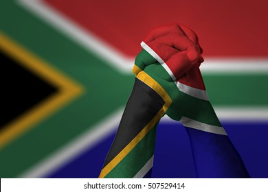 Man clasped hands patterned with the SOUTH AFRICA flag