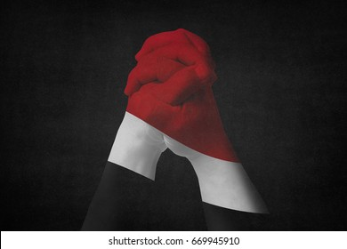 Man clasped hands patterned with the YEMEN flag,Black background.