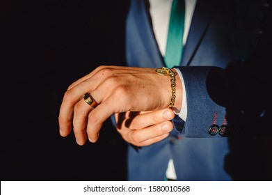 A man clasps a gold bracelet on his arm. Hands of successful businessman in tuxedo, closeup. Men's accessories, bracelet and gold ring on a man's hand.