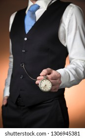 man with classic clothes showing the camera his pocket watch hanging from the vest