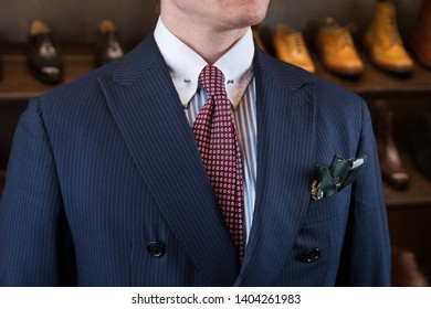 Man in classic fashion suit against luxury shoes boutique store display with variety of different models