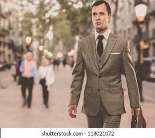 Man in classic grey suit with briefcase walking outdoors