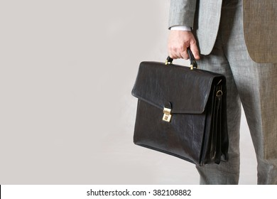 A man in a classical costume kept his black office leather bag. Closeup. Free space for a text.