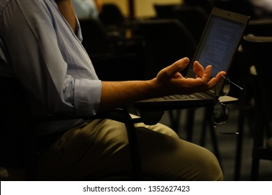 Man in classroom sitting with notebook in chair.