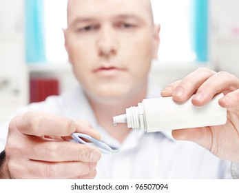 man clean contact lens at home, focus on drop of liquid from bottle