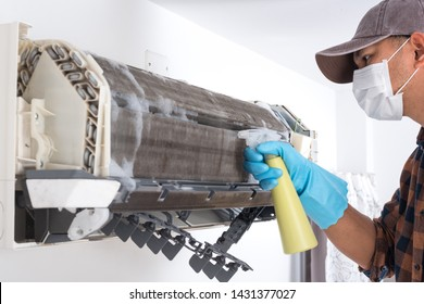 The man cleaning air conditioner indoor unit. Maintaining the air conditioner concept.