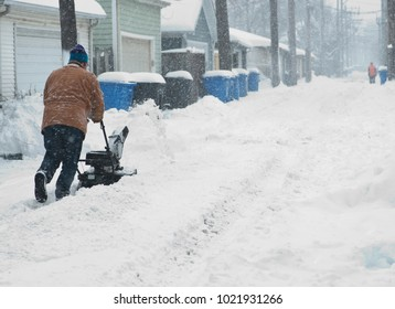 Man is cleaning alley before his garage, removing snow with snow blower.