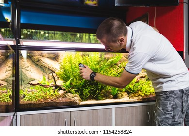 Man cleaning aquarium using magnetic fish tank cleaner.