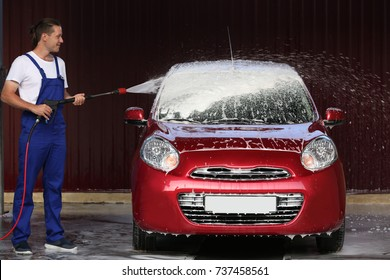 Man cleaning automobile with high pressure water at car wash