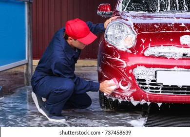 Man cleaning automobile with sponge at car wash