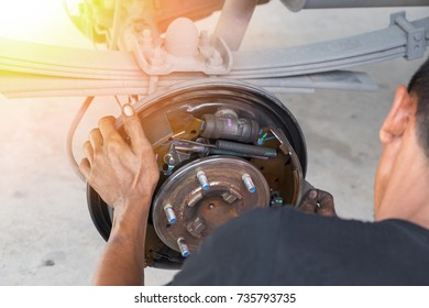 A man cleaning the brake drum with sandpaper.