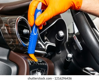 A man cleaning car with cloth and brush. Car detailing. Selective focus. Car detailing. Cleaning with brush. Worker cleaning. Brush and cleaning solution to clean.