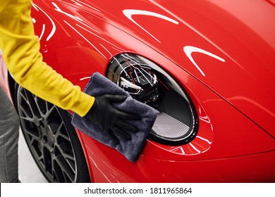 A man cleaning car with cloth, car detailing (or valeting) concept. Selective focus.