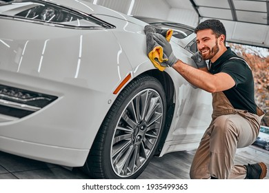 Man cleaning car and drying vehicle with microfiber cloth. Hand wipe down paint surface of shiny white car after polishing and ceramic coating. Car detailing and car wash concept. Selective fiocus.
