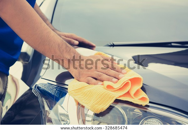 A man cleaning car with microfiber cloth, vintage tone image