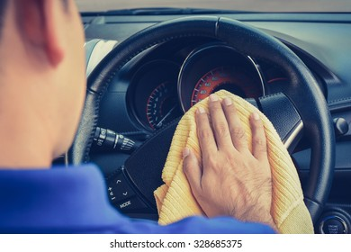 A man cleaning car steering wheel with microfiber cloth, vintage tone image
